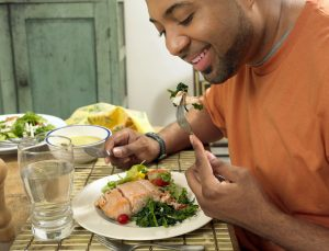 Man Sits at a Table at Home Eating a Salmon Salad for Lunch